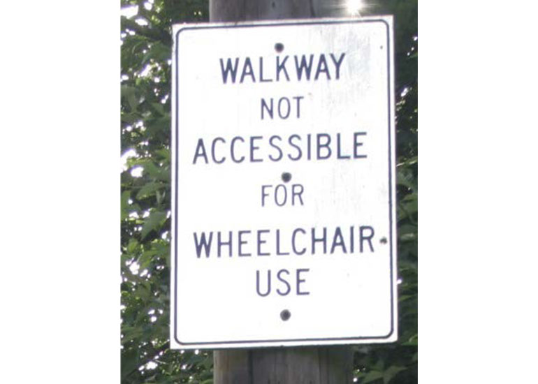 """A close-up view of a street sign that reads, """"walkway not accessible for wheelchair use."""""""